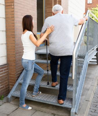 Woman helping elderly man with cane up stairs