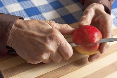 Woman cutting apple with knife